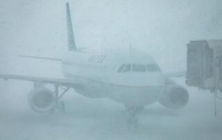 snow-covered plane at airport